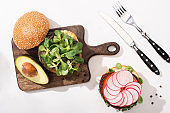 top view of vegan burgers with microgreens, avocado, radish on wooden cutting board on white background with cutlery