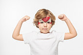 adorable boy with superhero mask painted on face demonstrating power isolated on white