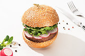 selective focus of delicious vegan burger with radish and arugula with black pepper on white background