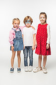full length view of cheerful kids and offended boy with colorful face paintings looking at camera on white background