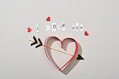 Top view of paper hearts with arrow and i love you lettering on grey background