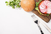 top view of vegan burger with microgreens, radish on wooden cutting board near cutlery on white background