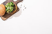 top view of vegan burger with microgreens on wooden board on white background