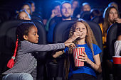 Multiracial friends enjoying cartoon in cinema hall.