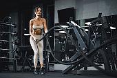 Fit brunette woman doing battle rope training.