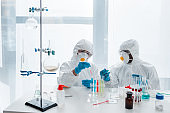 multicultural scientists in protective suits doing dna test in lab