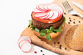 selective focus of delicious vegan burger with radish, tomato and microgreens on wooden boar with black pepper near fork and knife on white background