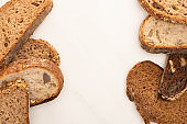 top view of fresh whole grain bread slices on white background with copy space