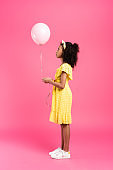 side view of curly african american child in yellow outfit with balloon on pink background
