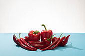 fresh red bell peppers and chili on blue surface on white background