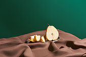 classic still life with cut pear on silver plate on table with brown tablecloth isolated on green