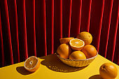 classic still life with oranges in wicker basket on yellow table near red curtain