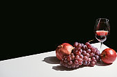 classic still life with fruits and red wine on white table isolated on black