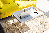 living room with yellow sofa and table with laptop, smartphone and notepad in sunlight