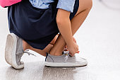 cropped view of schoolgirl tying laces on gumshoe
