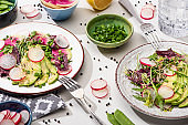 fresh radish salad with greens and avocado on plates on white surface with ingredients in bowls and water