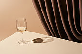 classic still life with glass of white wine on table near curtain isolated on beige