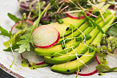 close up view of fresh radish salad with greens and avocado