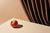 classic still life with pomegranate on table near curtain isolated on beige