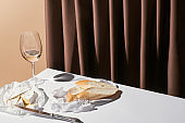 classic still life with baguette, Camembert cheese and white wine on table near curtain isolated on beige