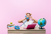 Schoolkid talking on smartphone and telephone near books and globe isolated on pink