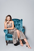 elegant woman in dress posing on armchair isolated on grey