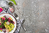 top view of fresh radish salad with greens and avocado on grey concrete surface with glass of water, fork and napkin