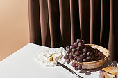 classic still life with grape in basket, brie cheese and baguette on table near curtain isolated on beige