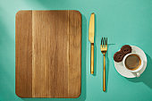 Top view of wooden cutting board with cutlery, coffee and cookies on turquoise surface