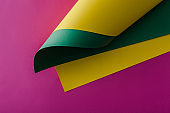 yellow and green paper swirl on purple background