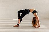 flexible woman doing wheel pose in yoga studio