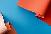 orange colorful paper swirls on blue background