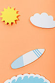 Top view of paper cut sun, cloud, surfboard and sea wave on orange background