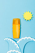 Top view of paper cut sun and sea waves with dispenser bottle of sunscreen on blue background