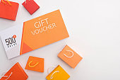 Top view of gift voucher near toy shopping bags on white surface