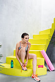 Selective focus of sportswoman tying lace on sneaker near bottle of water and sport equipment on stairs at home