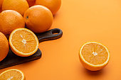 ripe delicious cut and whole oranges on wooden cutting board on colorful background
