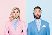 shocked woman and handsome man looking at camera on pink and blue background