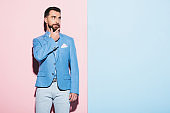 thoughtful man looking away on pink and blue background