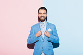 smiling man looking at camera on pink and blue background