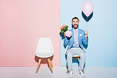 handsome and smiling man holding balloon, gift and on bouquet blue and pink background