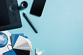 Top view of graphics tablet, smartphone, color samples and watercolor drawing on blue background