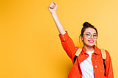 excited student in eyeglasses showing winner gesture while smiling at camera on yellow background
