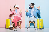 shocked woman and man in virtual reality headsets on pink and blue background