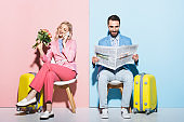 attractive woman talking on smartphone and smiling man reading newspaper on pink and blue background