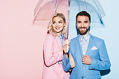 smiling woman and handsome man with umbrella on pink and blue background