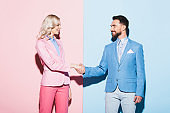 smiling woman and handsome man shaking hands on pink and blue background