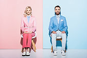 smiling woman and handsome man looking at camera on pink and blue background