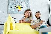selective focus of bored homosexual men watching movie in living room