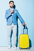 man drinking cocktail and holding travel bag on blue background